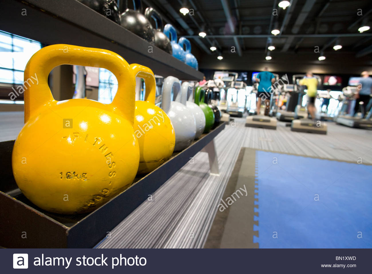 Colorful medicine balls on rack in health club and people exercising in background - Stock Image