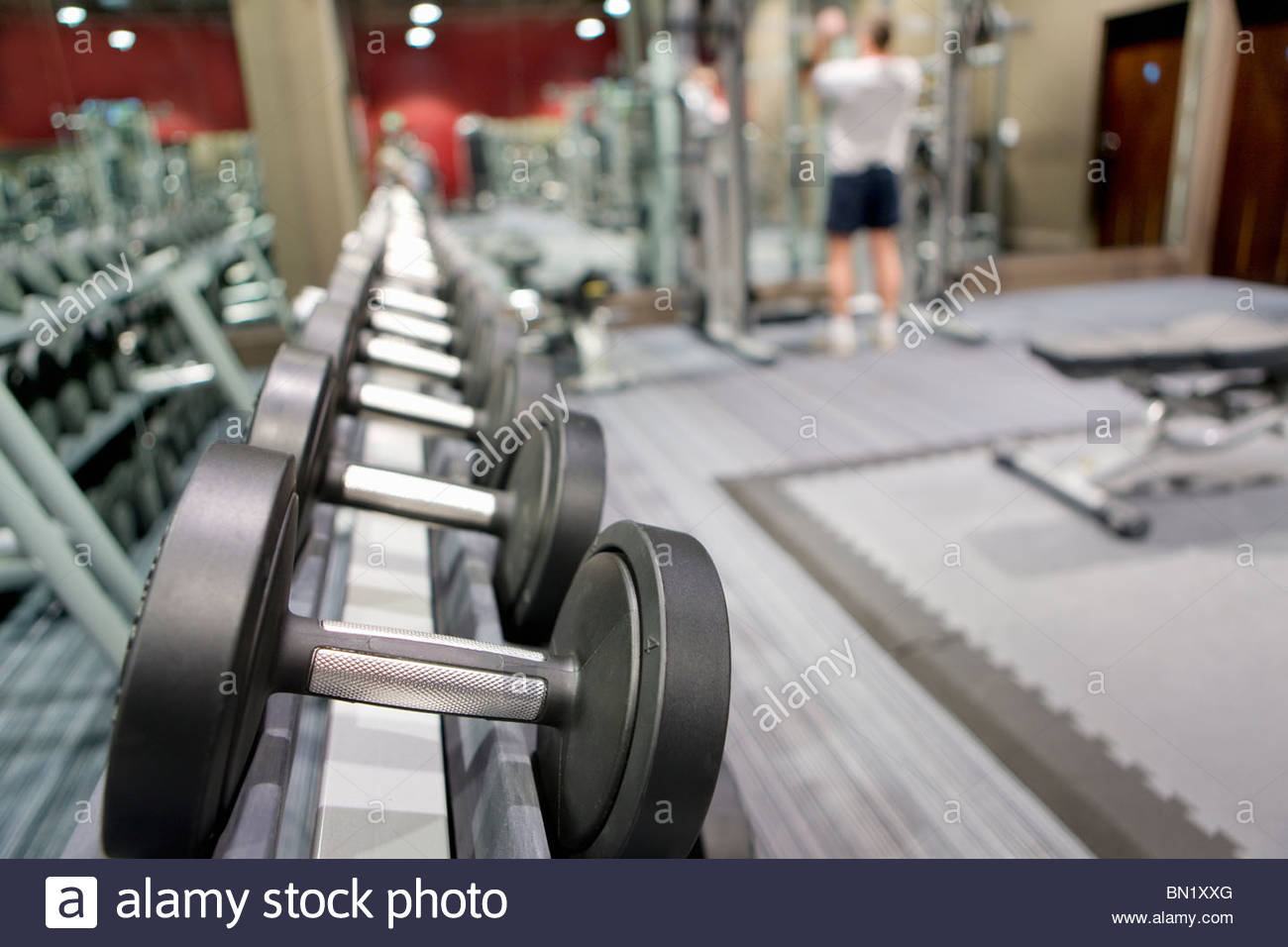 Rack of dumbbells in health club with man lifting weights in background - Stock Image