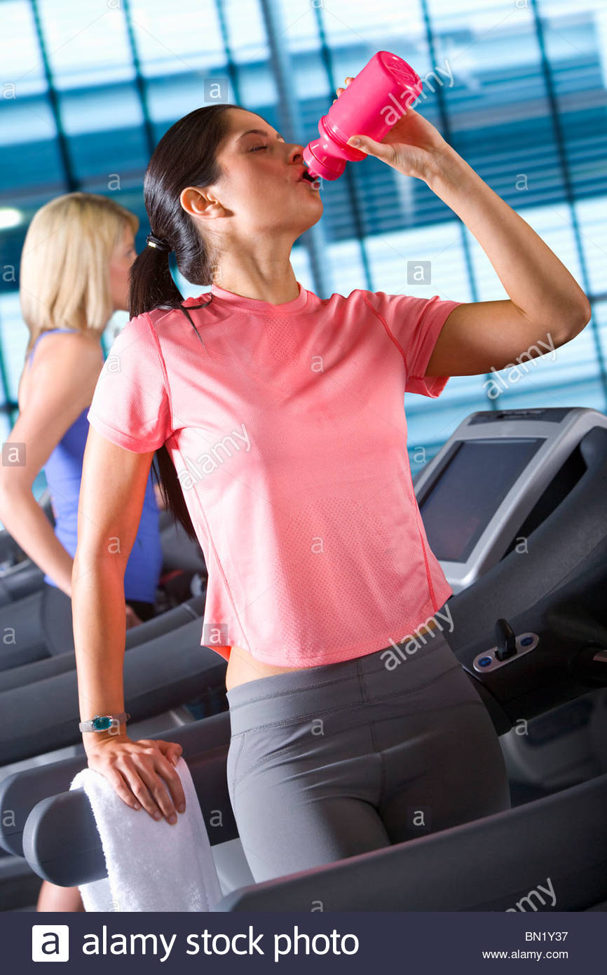 Woman drinking from water bottle on treadmill in health club - Stock Image