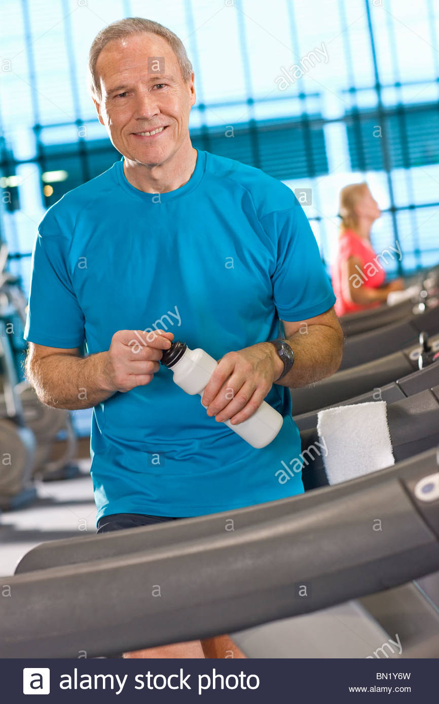 Portrait of smiling man with water bottle leaning on treadmill in health club - Stock Image