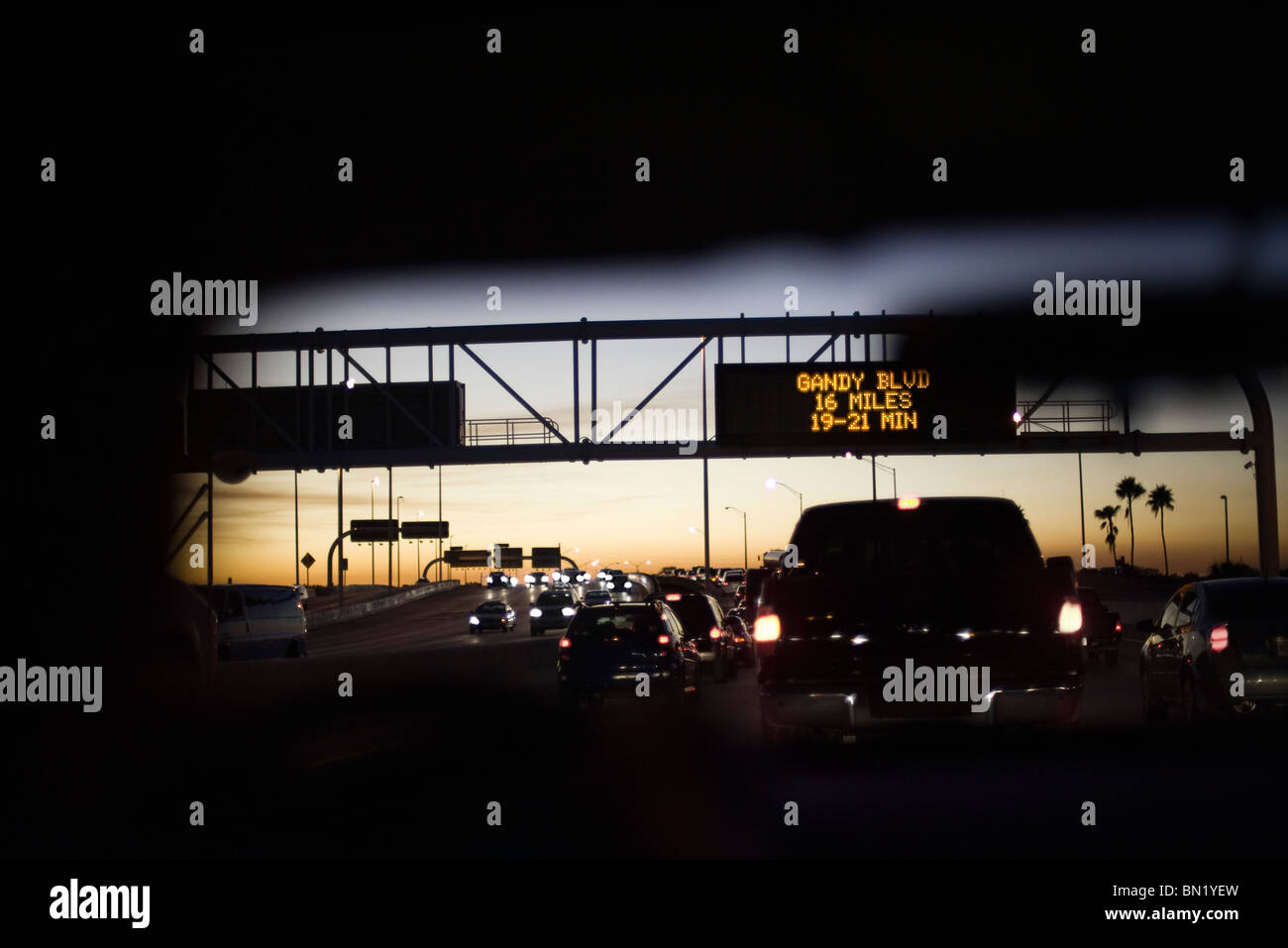 Driving in traffic at sunset - Stock Image