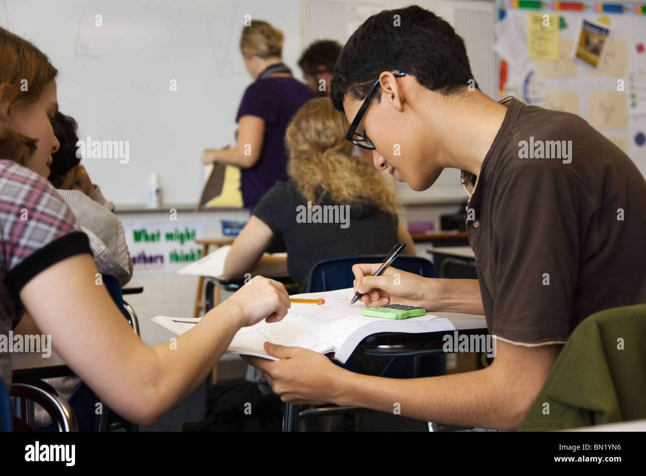High school student helping classmate with assignment - Stock Image