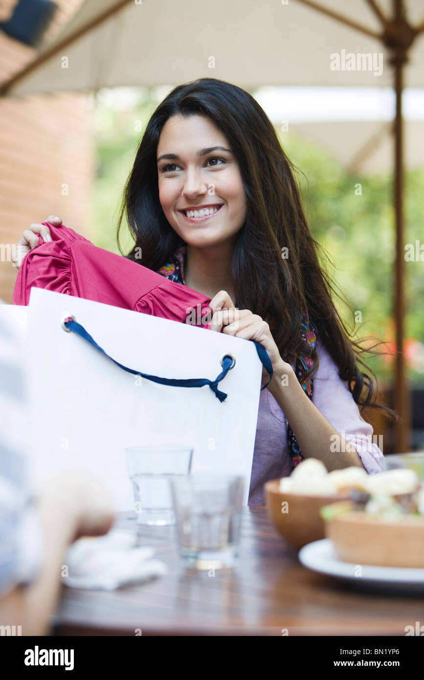 Woman sitting in cafe with friend, showing clothing in shopping bag - Stock Image