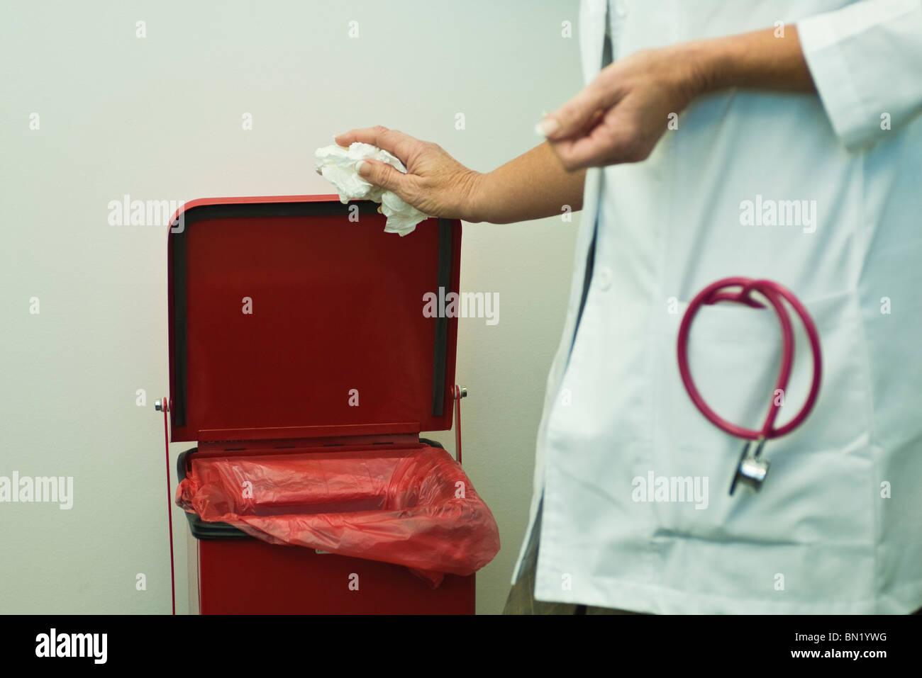 Discarding waste in medical waste bin - Stock Image