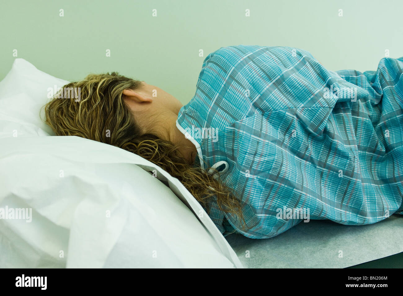 Female patient lying on side on examination table - Stock Image