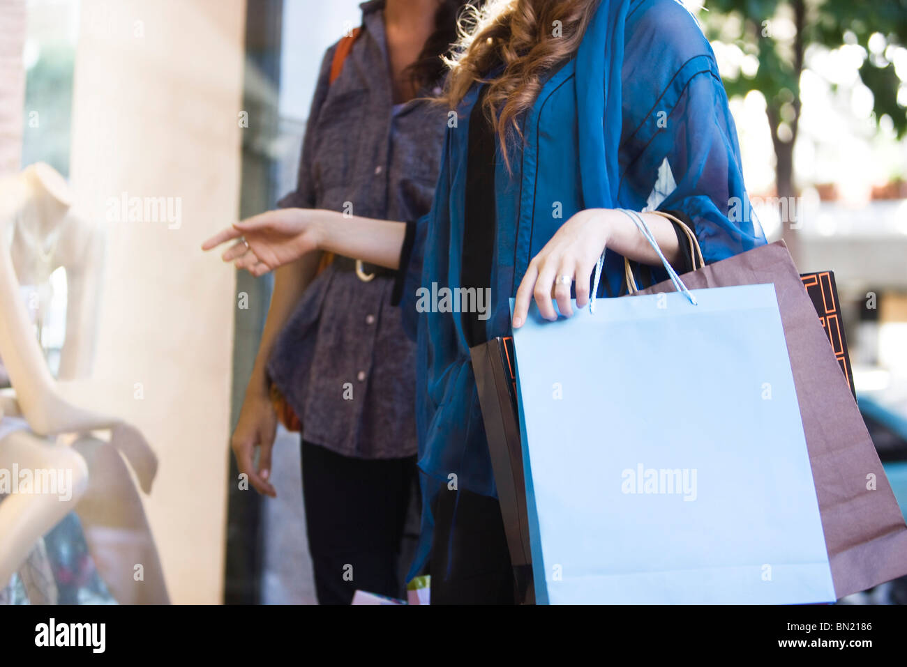 Shoppers looking in shop window, cropped - Stock Image