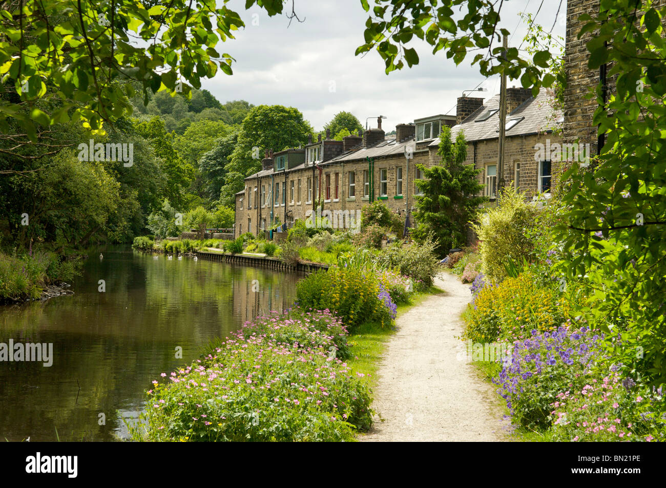 Stone built terraced houses on the banks of the rochdale canal at Hebden Bridge Yorkshire - Stock Image