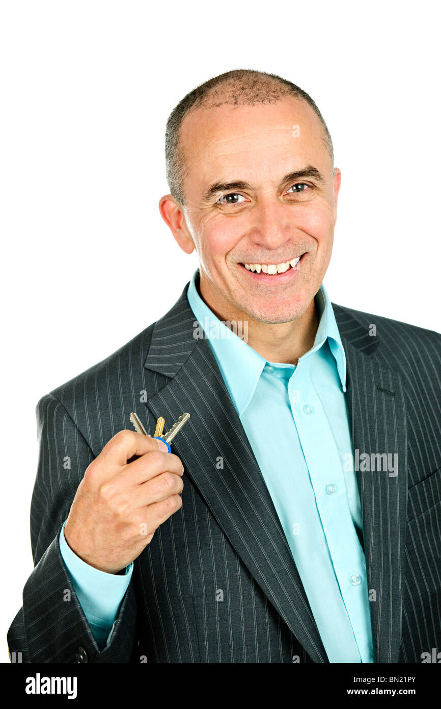 Portrait of smiling businessman holding keys isolated on white background - Stock Image