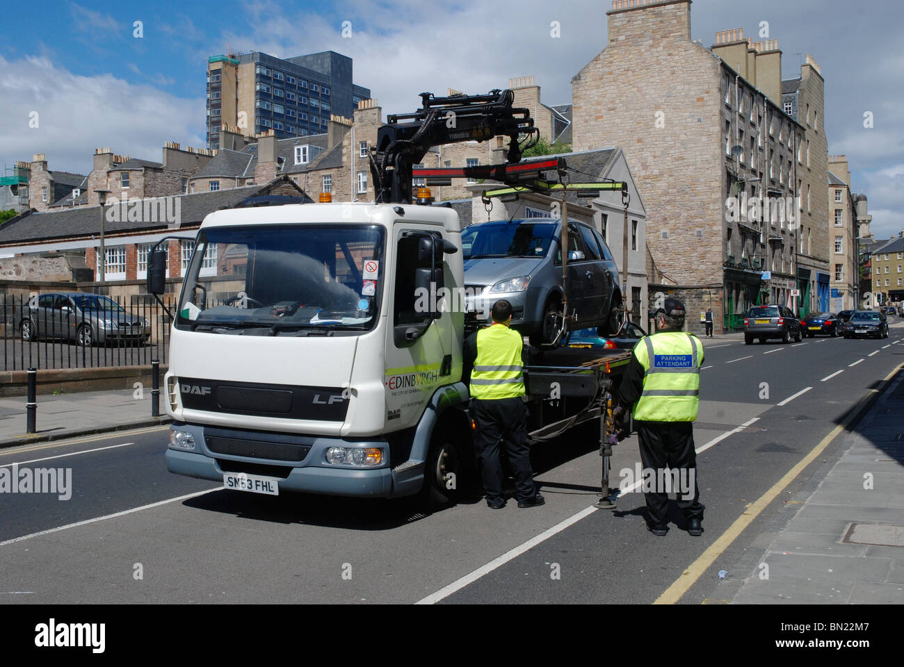 Staff from Edinburgh City Council impound an illegally parked car. - Stock Image