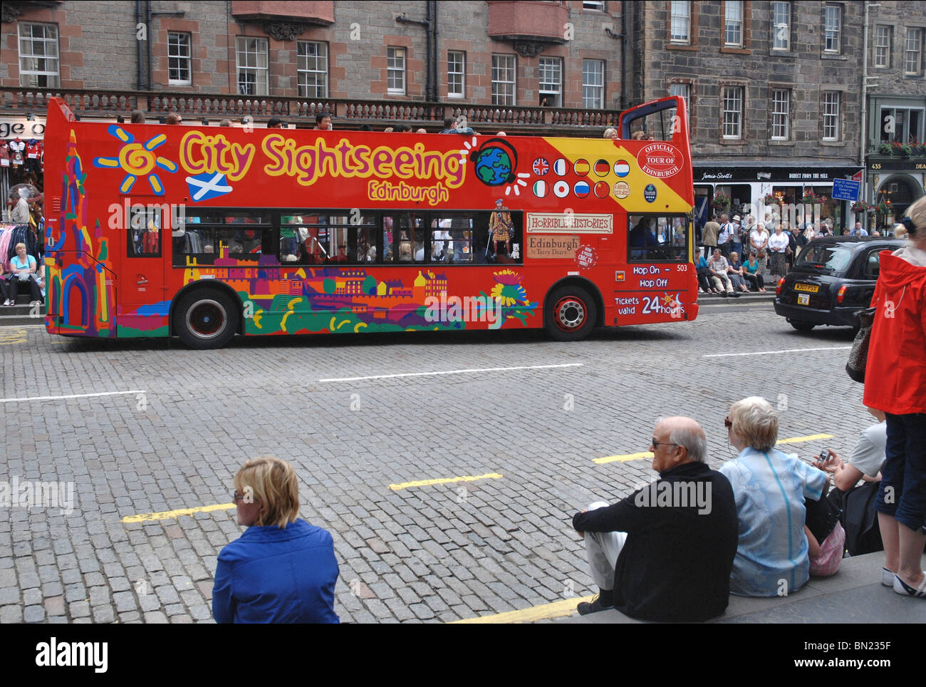 Sightseeing bus making its way down the Royal Mile (High Street) in Edinburgh. - Stock Image