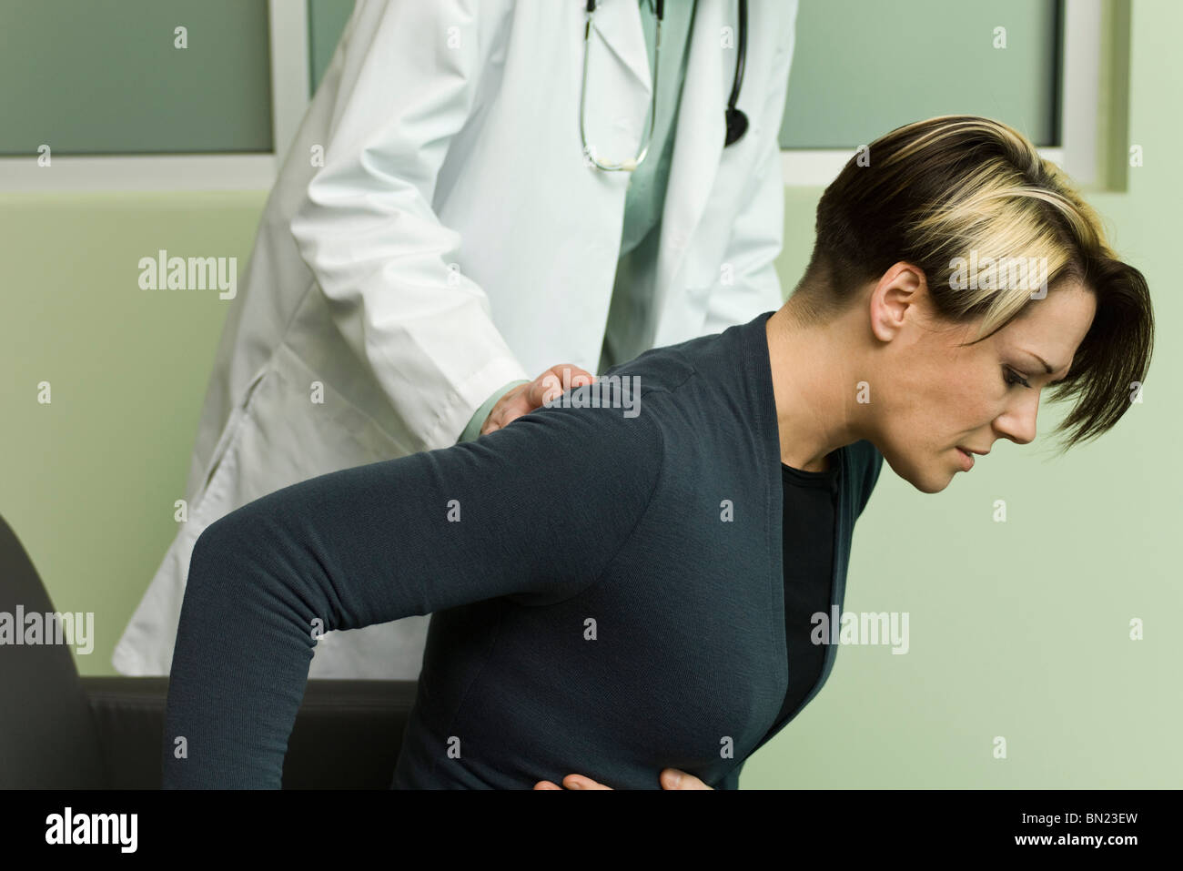 Doctor assisting patient experiencing severe abdominal pain - Stock Image