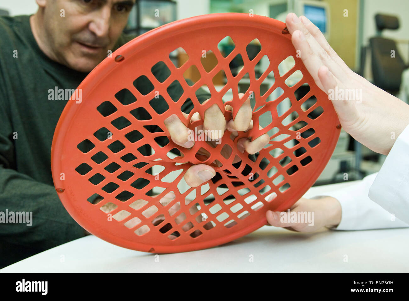 Patient using hand exercise web for occupational therapy treatment - Stock Image
