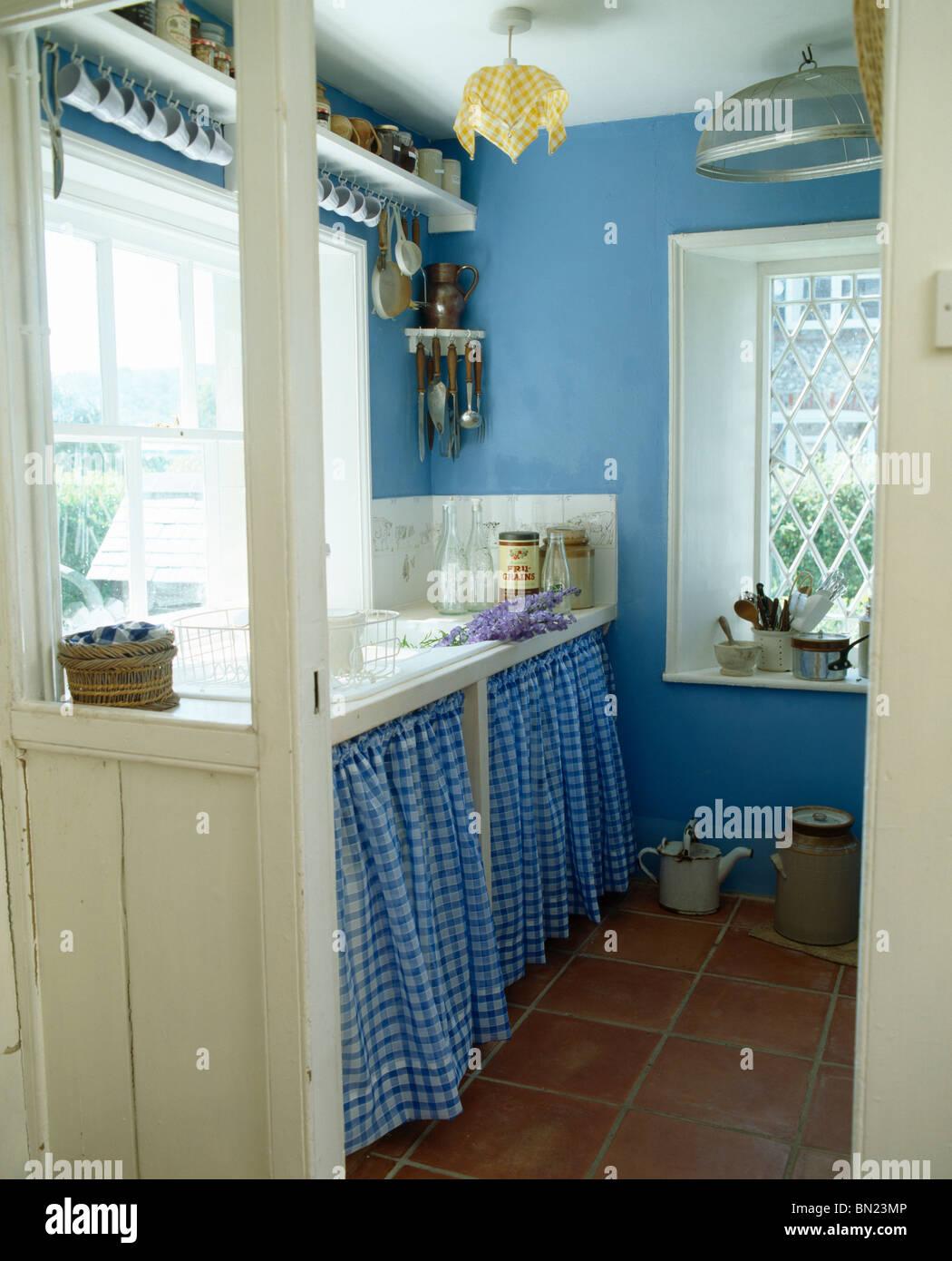 Blue checked curtains on cupboard below sink in blue cottage kitchen ...