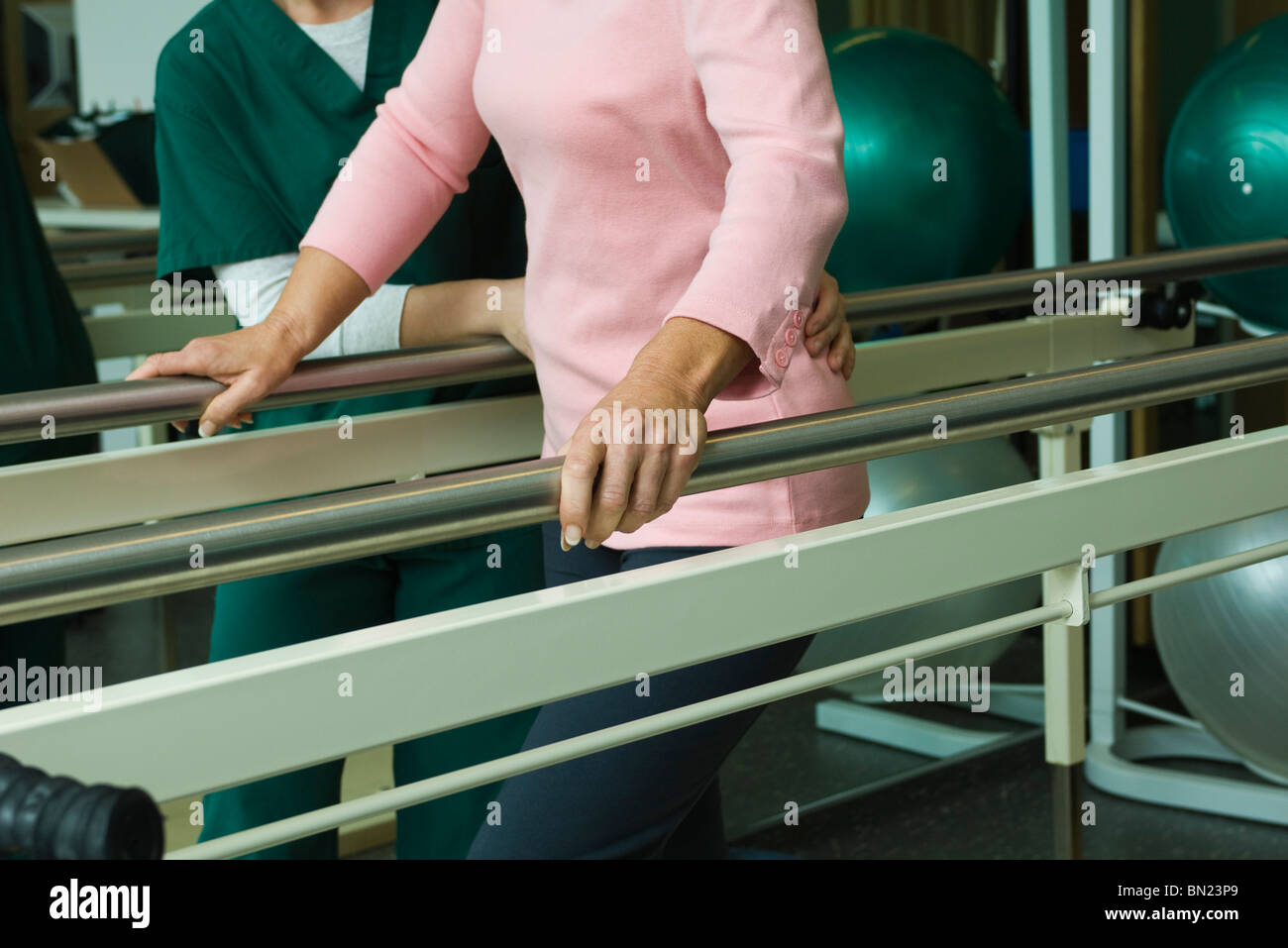 Patient undergoing post-surgery rehabilitation exercises to regain ability to walk - Stock Image