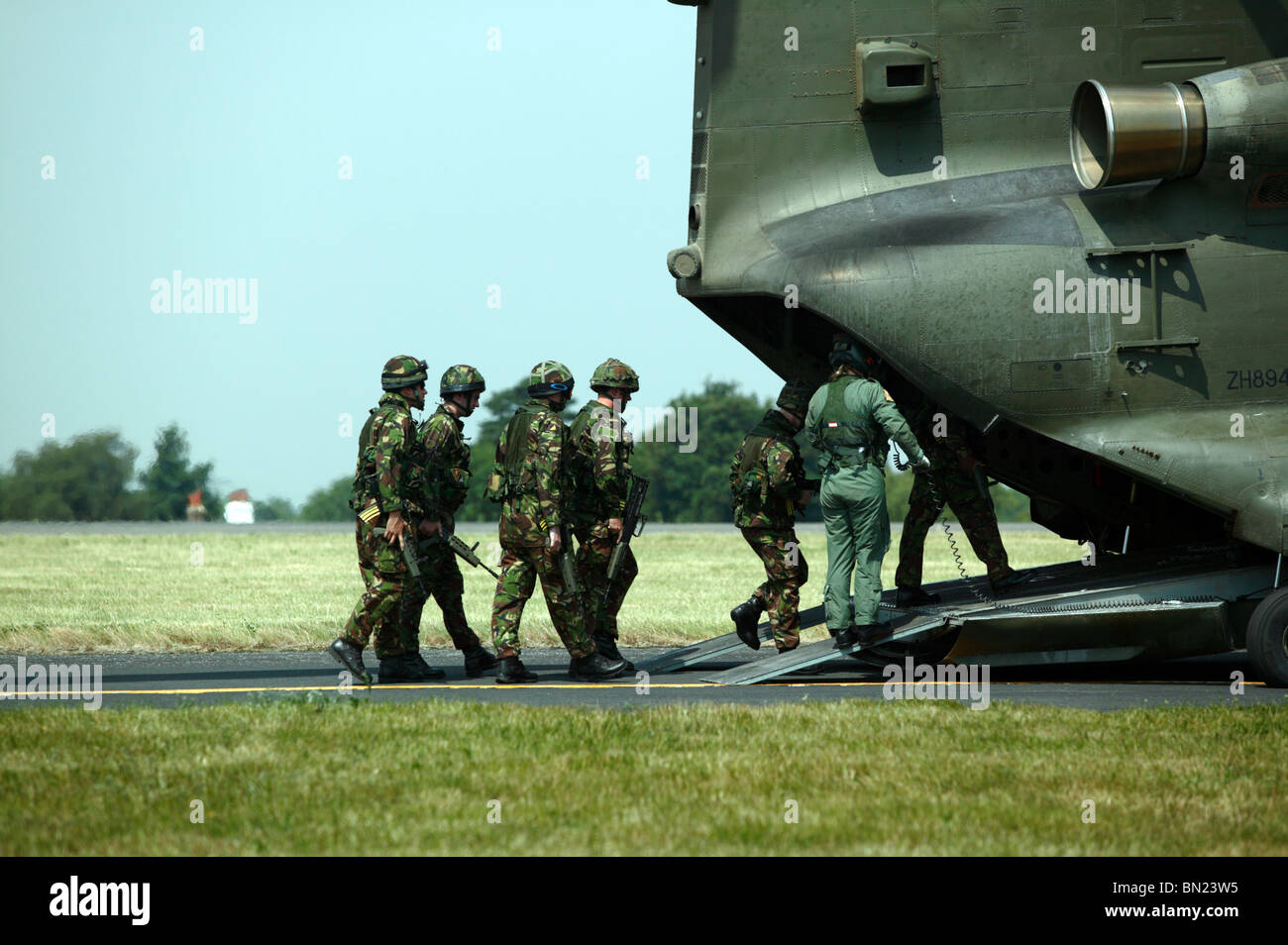 Troops boarding an RAF Chinook HC.2 helicopter, via its rear loading ramp, under the guidance of an air loadmaster. - Stock Image