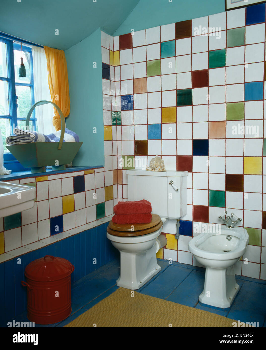 Multi-colored wall tiles above bidet and toilet in pale turquoise ...