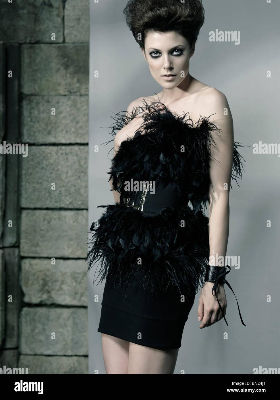 High fashion photo of a beautiful woman wearing elegant black feathery dress - Stock Image