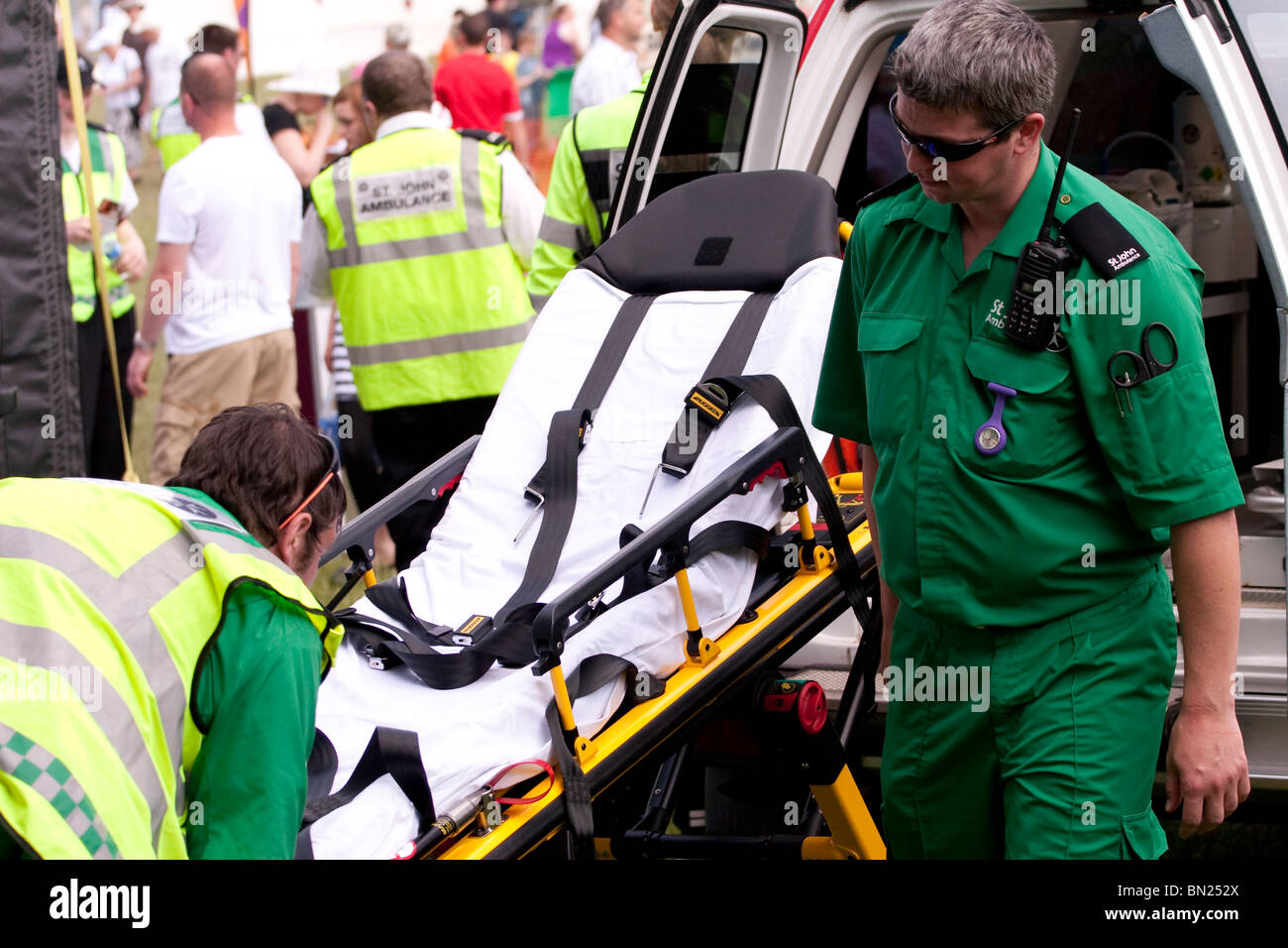 Two paramedics lifting a stretcher in to the back of an ambulance - Stock Image