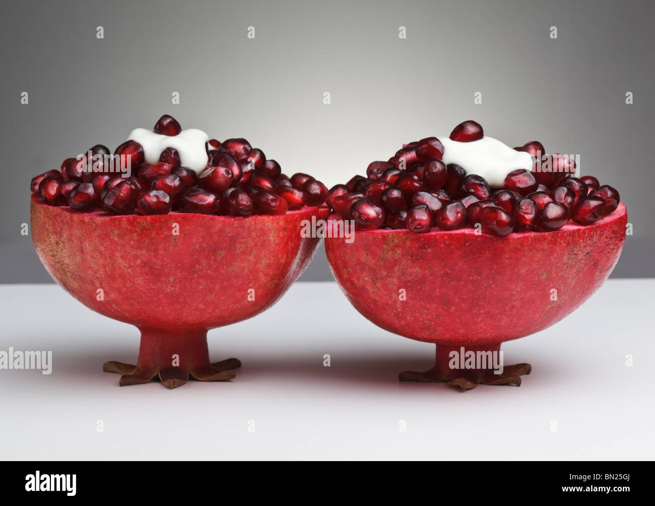 Two cut Pomegranates filled with juicy seeds and topped with Yogurt Stock Photo