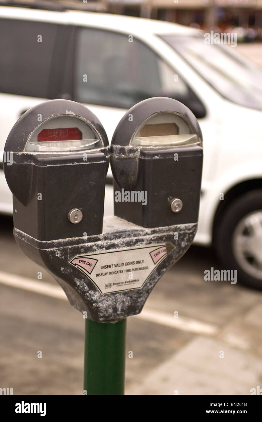 An expired parking meter with a car in the background - Stock Image