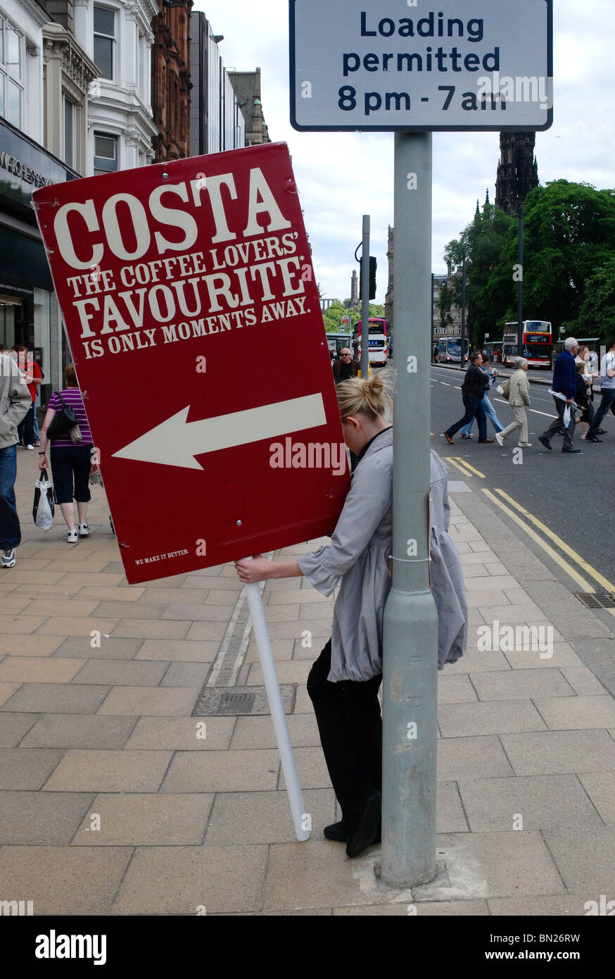 A girl holds an advertising sign for Costa Coffee on Princes Street, Edinburgh. - Stock Image