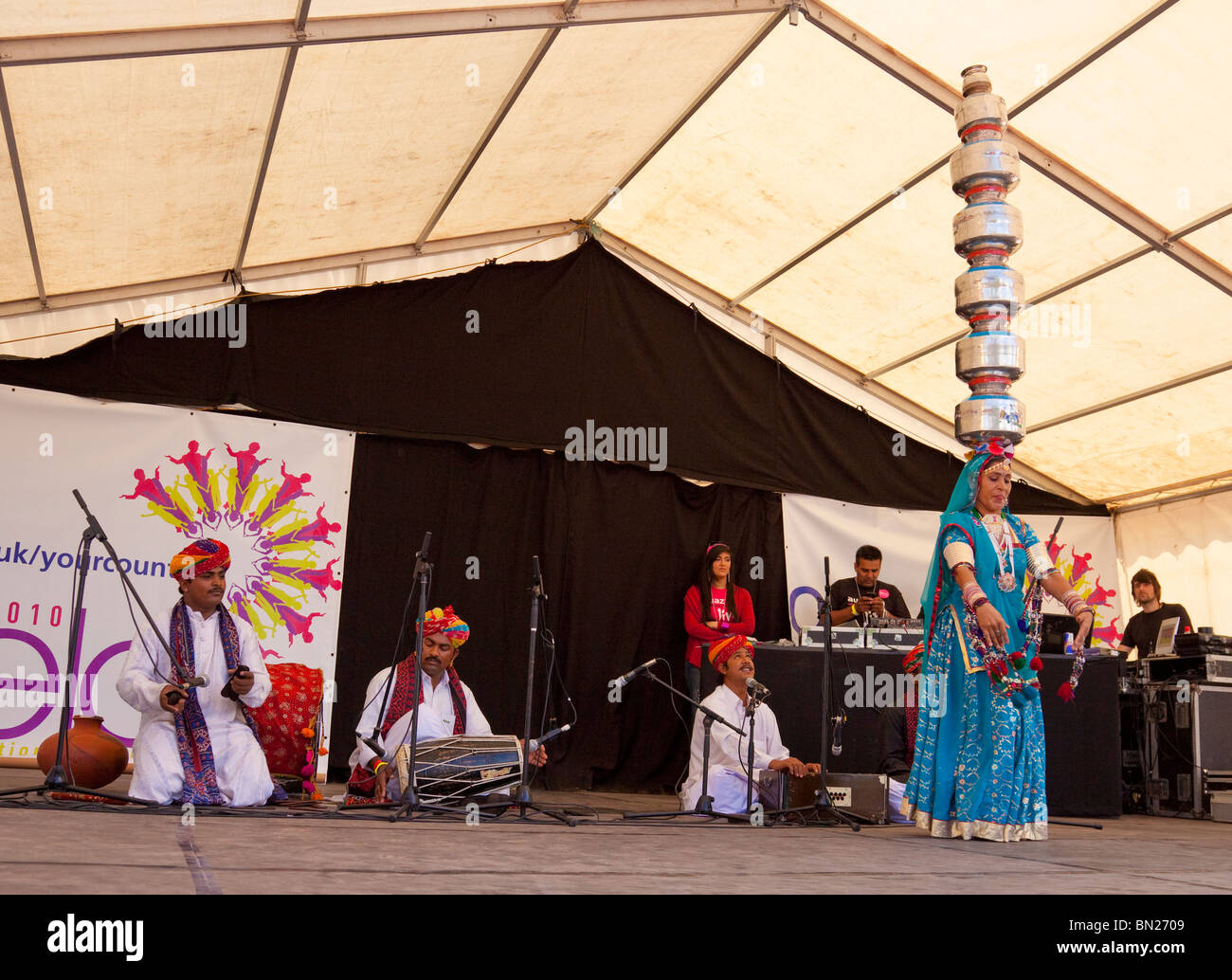 Traditional Rajashtani Bhavai dancer balancing seven metal pots on her head while dancing; musicians on stage, Glasgow - Stock Image