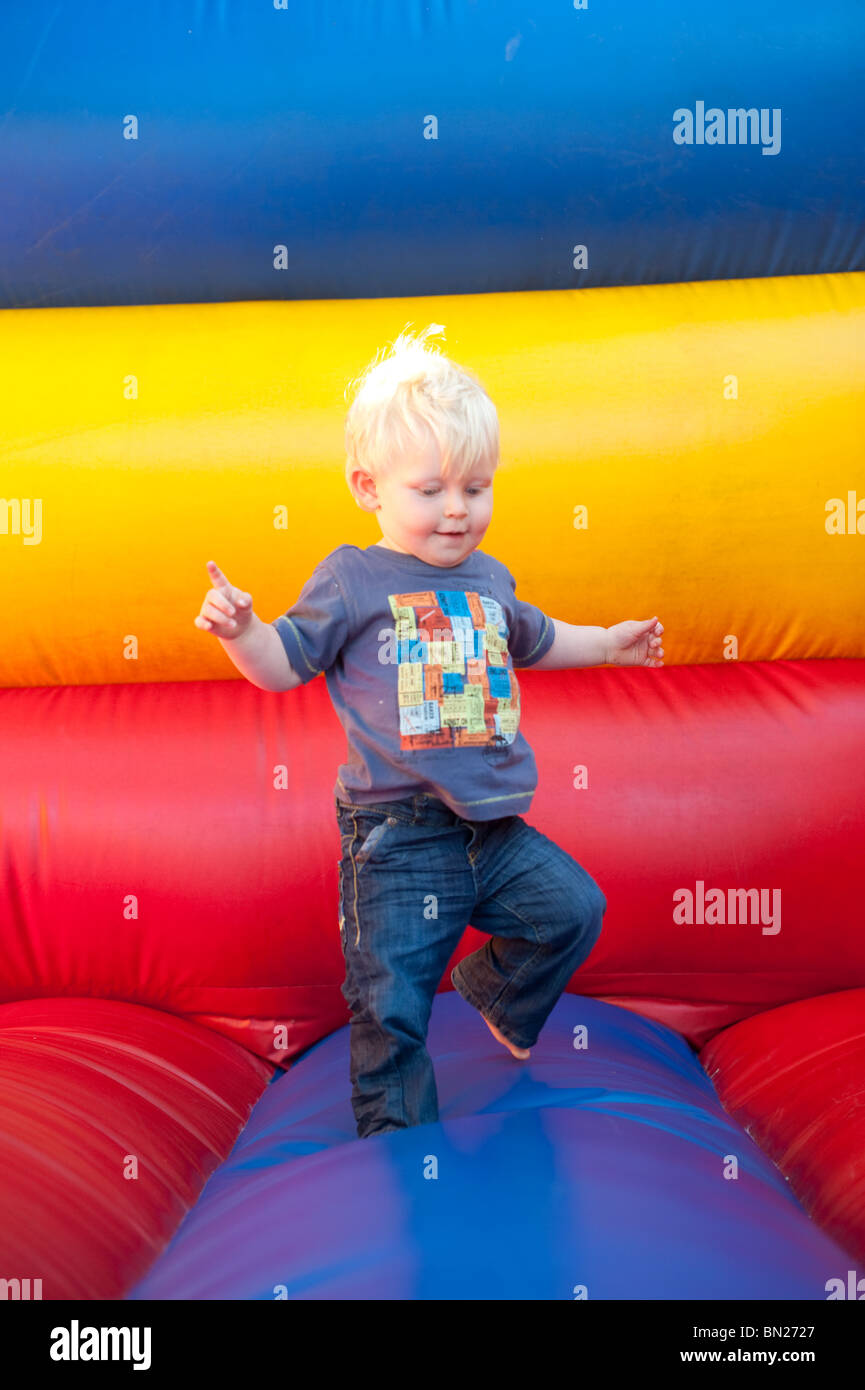 Boy Toddler tentatively walking on bouncy castle - Stock Image