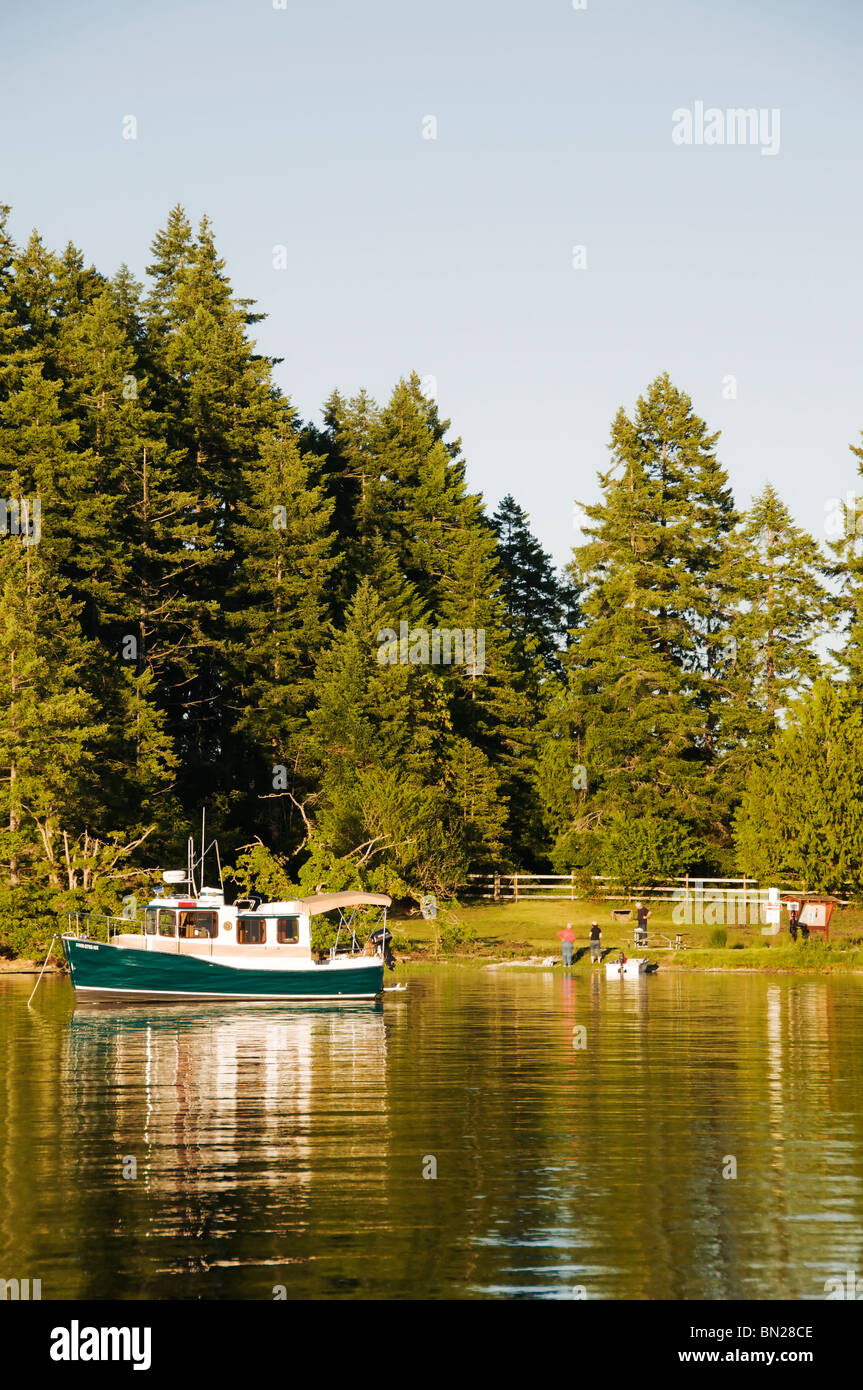A charming tug shaped boat is anchored near McMicken Island State Park at high tide in Case Inlet on south Puget - Stock Image