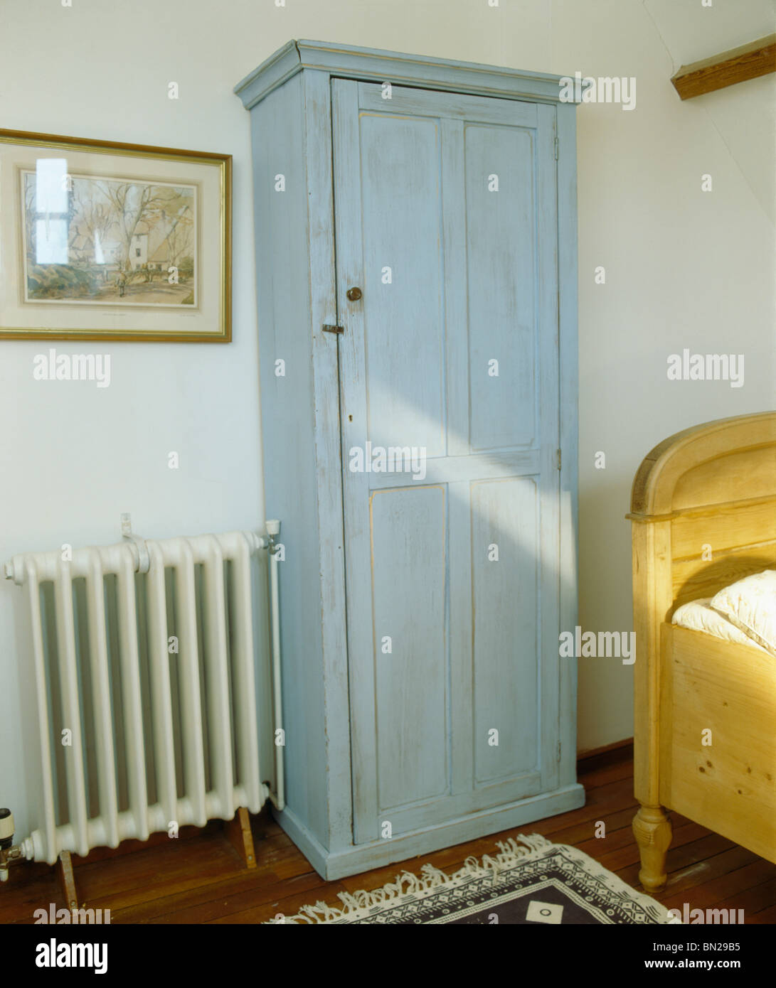 Painted Blue Wardrobe Beside Radiator In Small Country Bedroom Stock Photo Alamy
