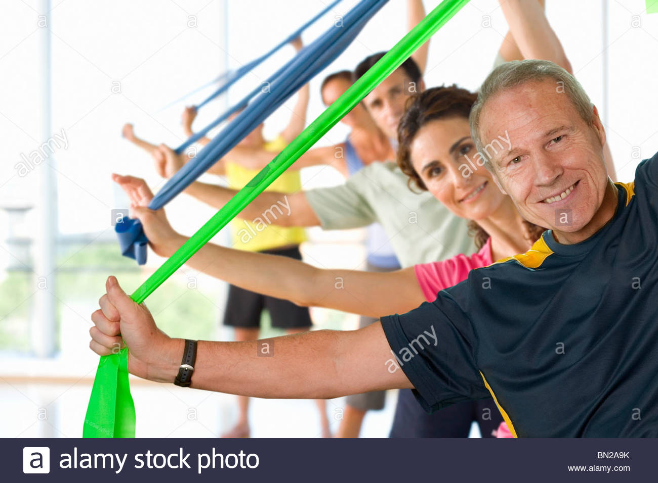 Men and women holding resistance bands overhead in exercise glass - Stock Image