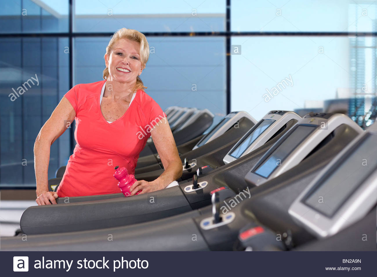Portrait of smiling senior woman with water bottle on treadmill in health club - Stock Image