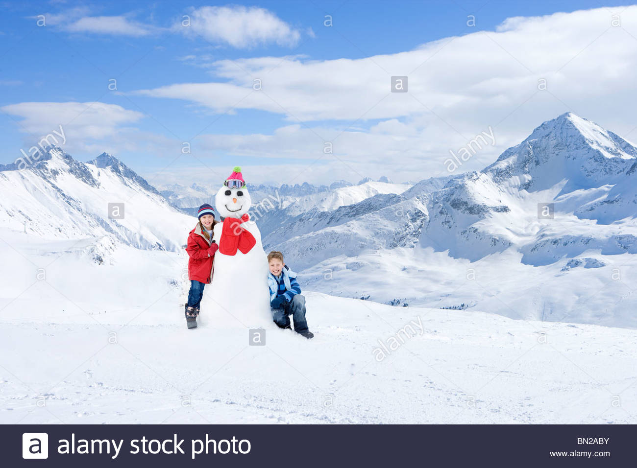 Portrait of boy and girl with snowman on snowy mountain - Stock Image