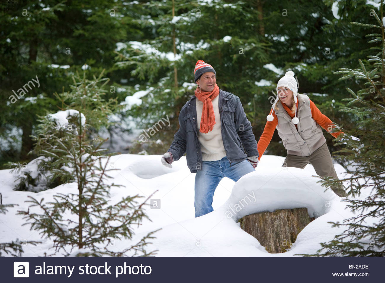 Playful couple holding hands in snowy woods - Stock Image