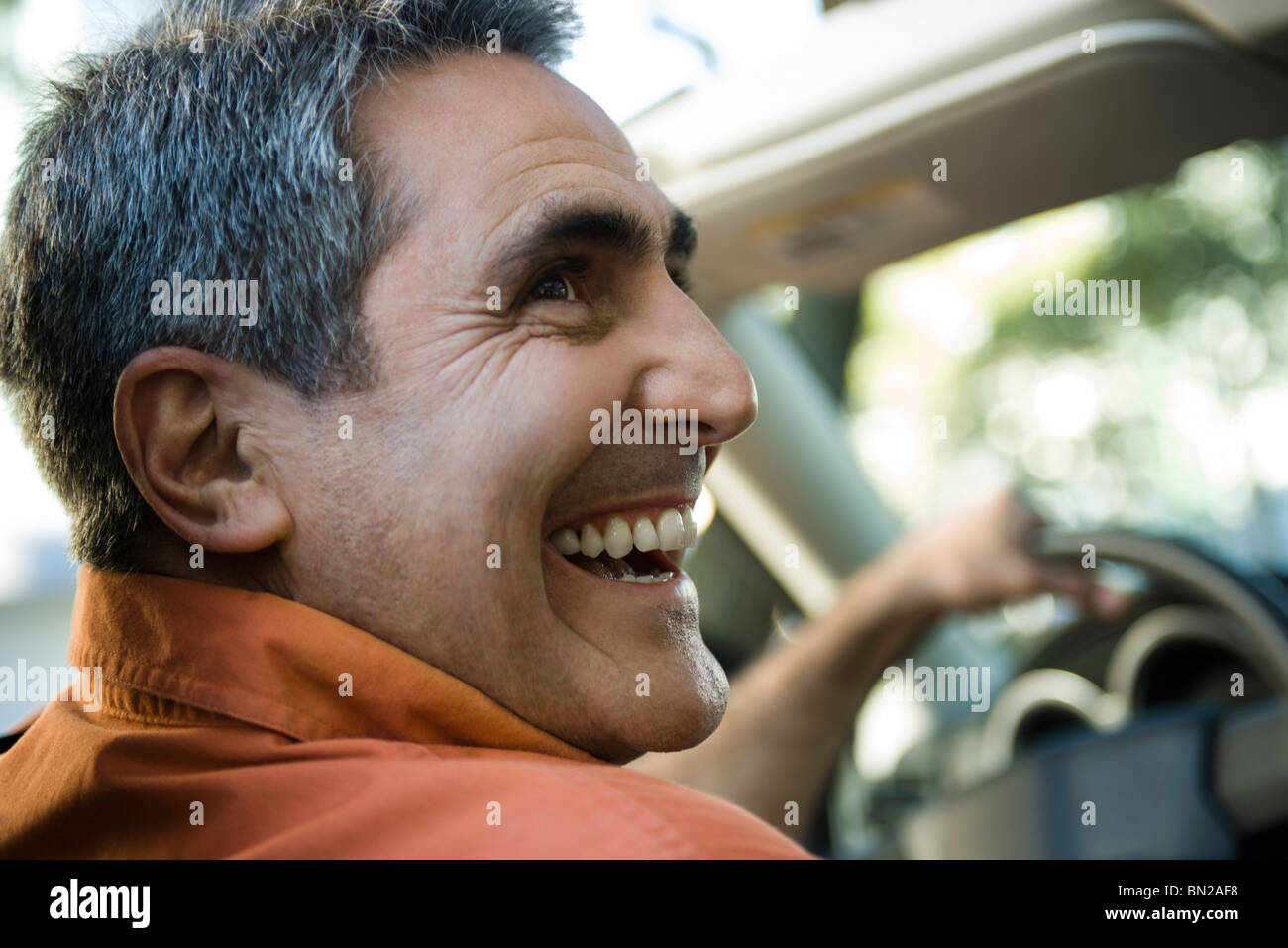 Mature man driving with look of happiness - Stock Image