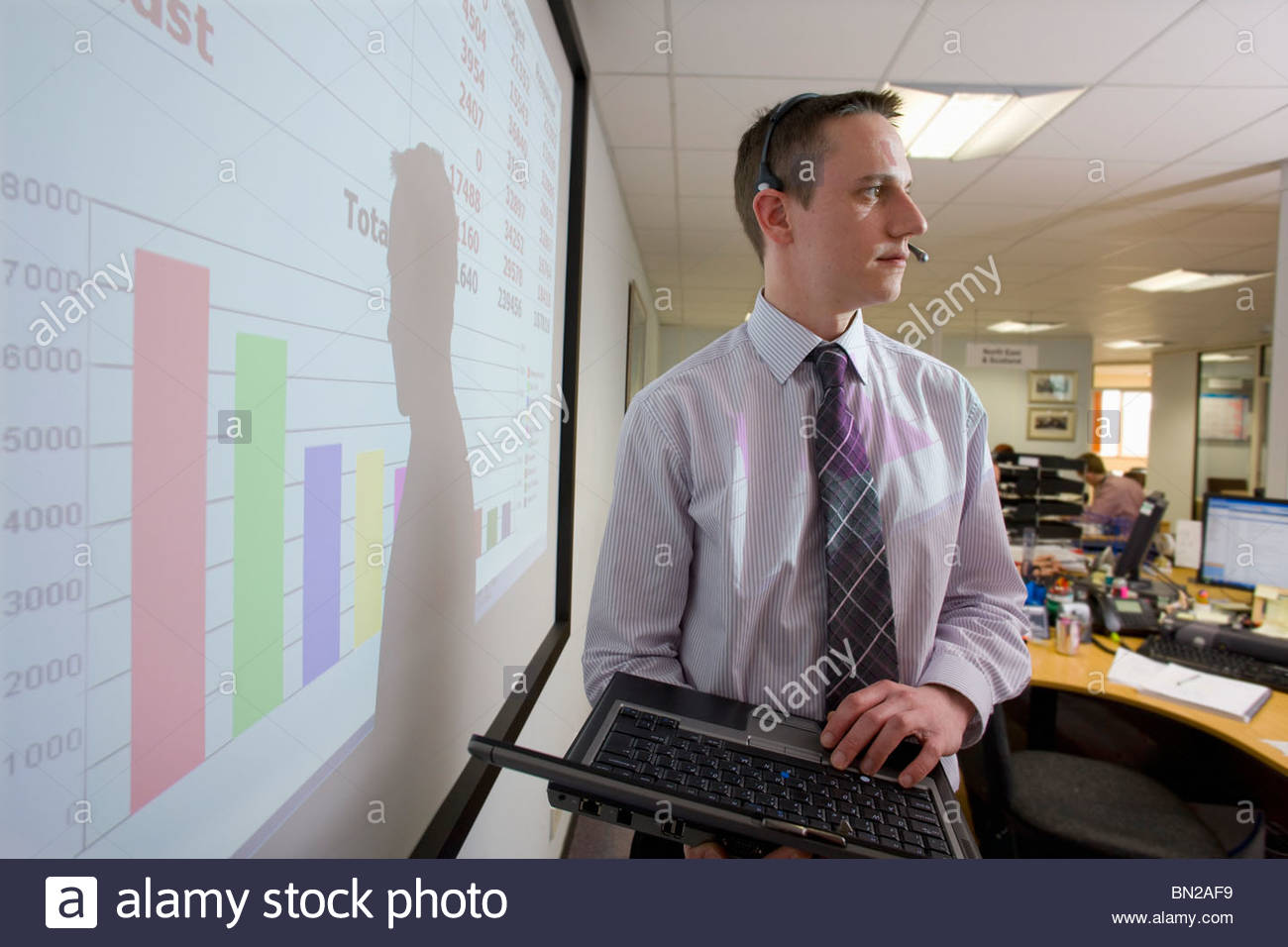 Businessman wearing headset and holding laptop in front of data on projection screen - Stock Image