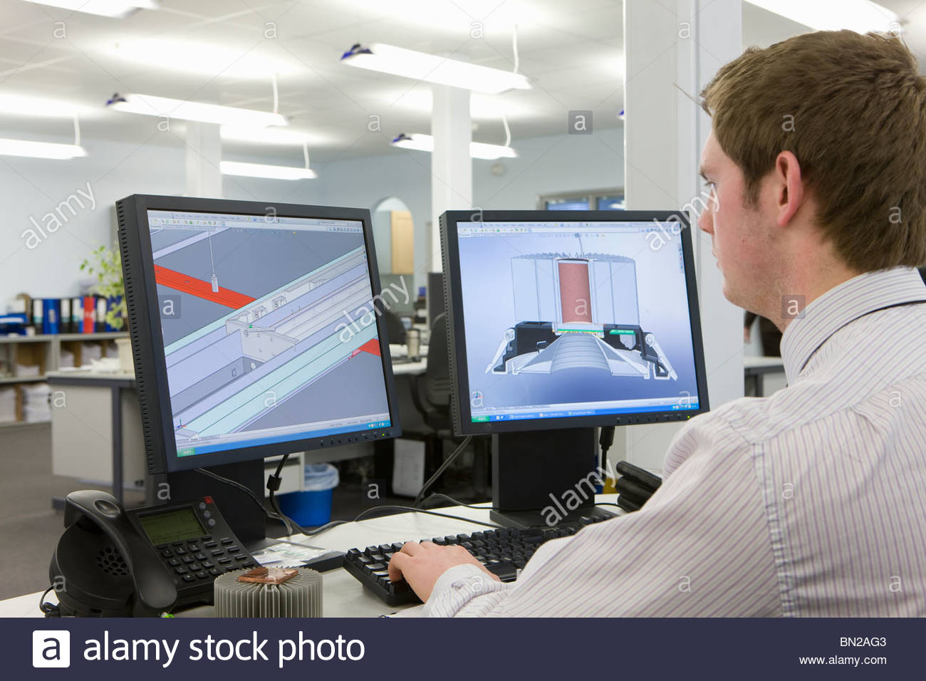 CAD designer working at computer monitors in office - Stock Image