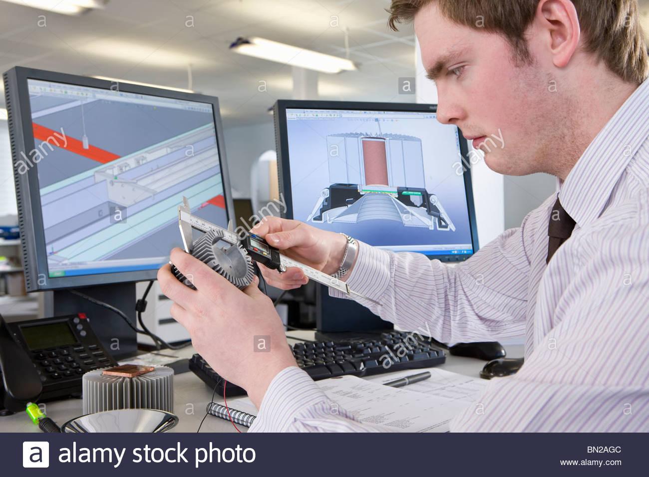 CAD designer measuring part at desk in office - Stock Image