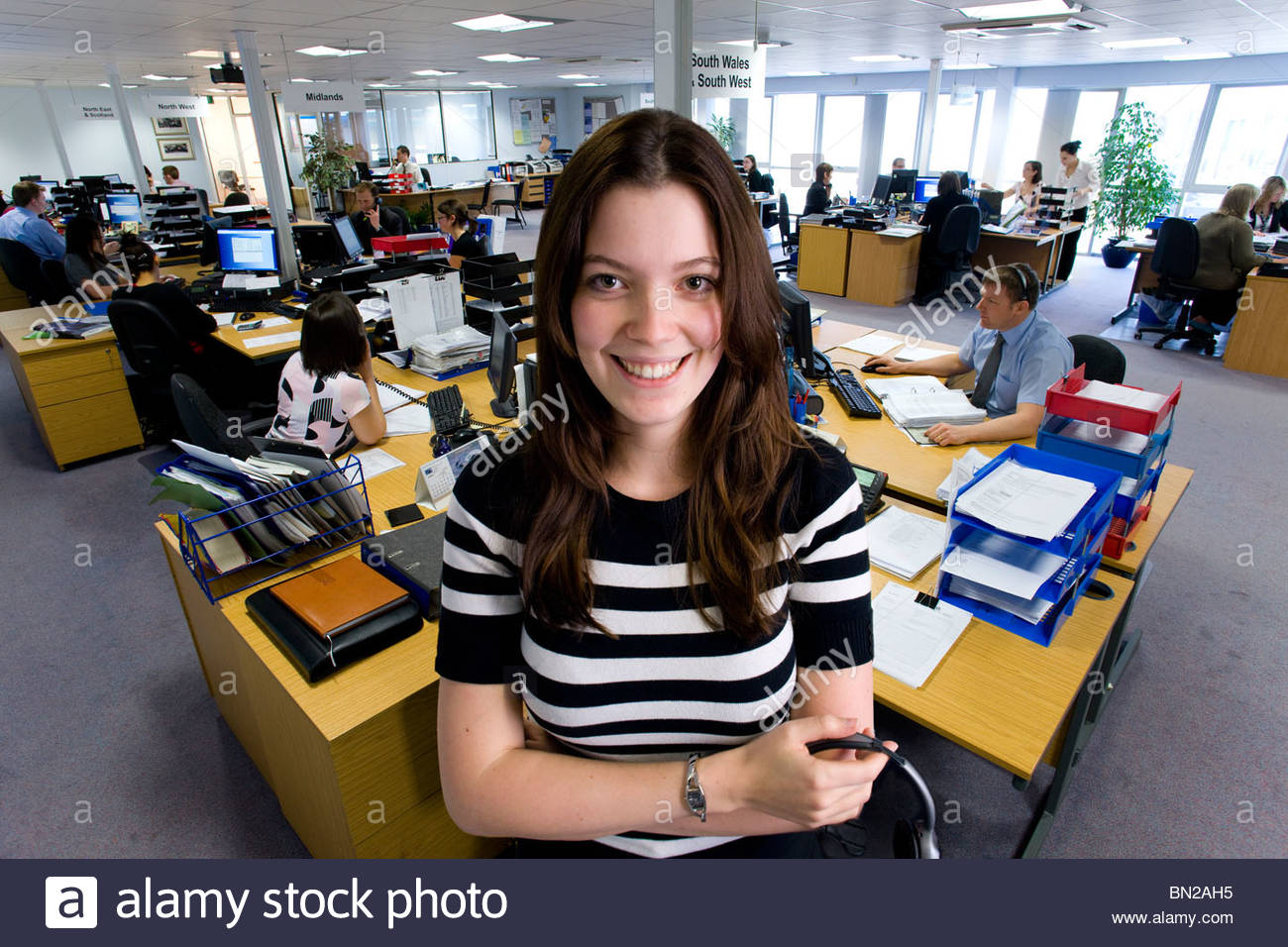Smiling saleswoman in call center office - Stock Image