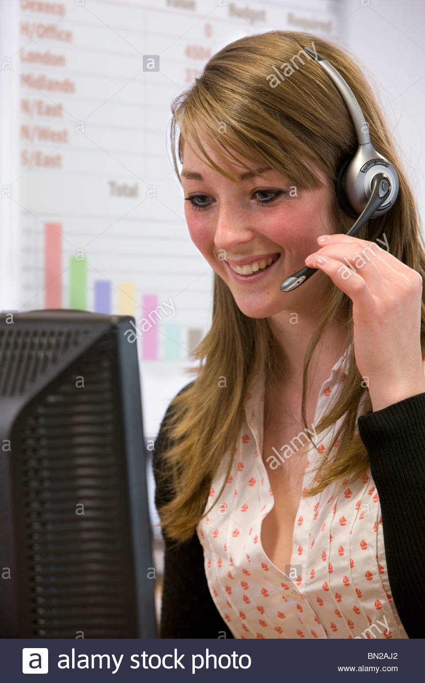 Saleswoman talking into headset and working at computer - Stock Image