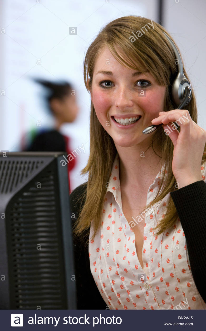 Smiling saleswoman wearing headset at computer - Stock Image