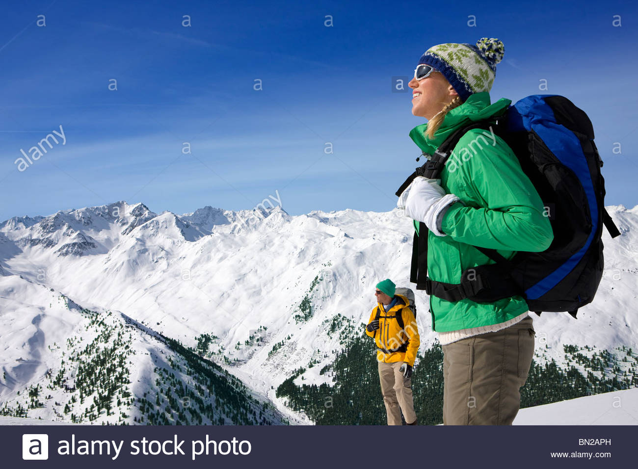 Couple backpacking on snowy mountain - Stock Image
