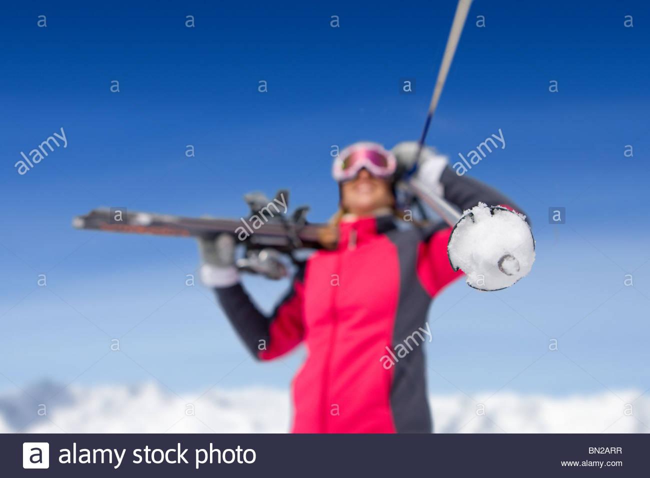 Woman holding skis and ski poles - Stock Image