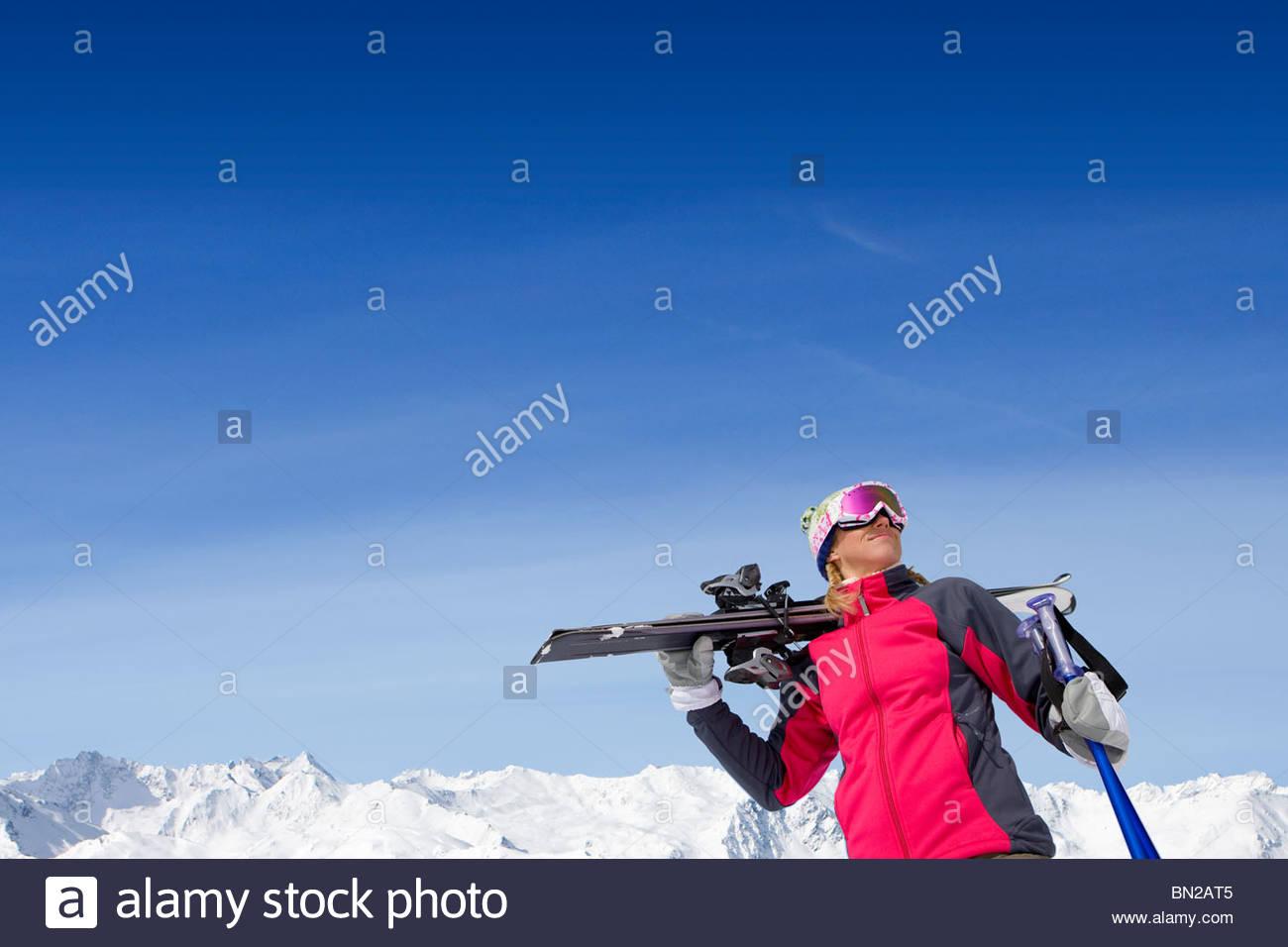 Woman holding skis and ski poles on snowy mountain - Stock Image