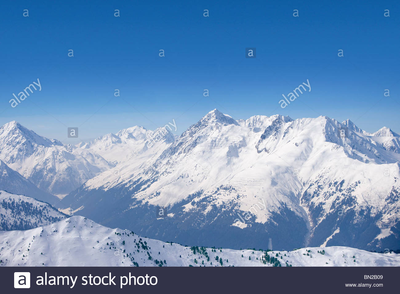 Snowy mountain range and blue sky - Stock Image