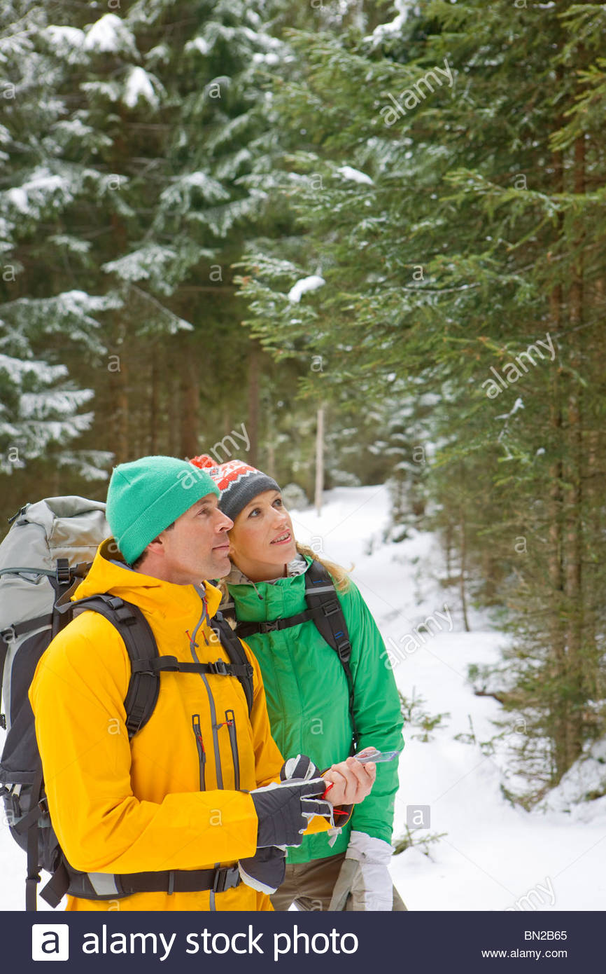 Couple with backpacks holding compass in snowy woods - Stock Image
