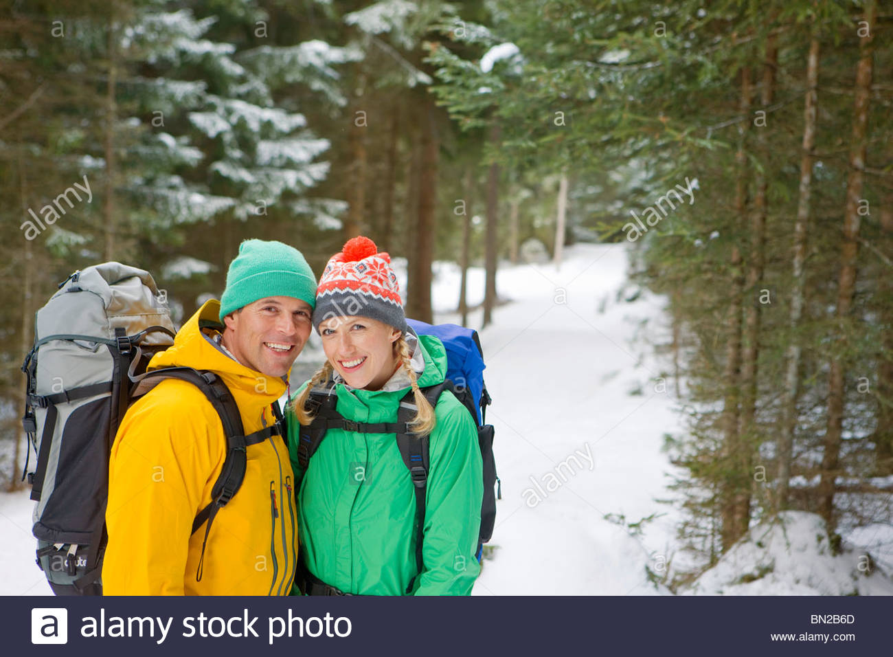 Portrait of happy couple with backpacks in snowy woods - Stock Image