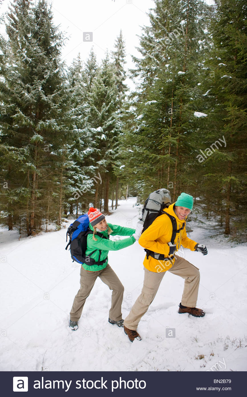 Woman pushing man with backpack up snowy slope in woods - Stock Image