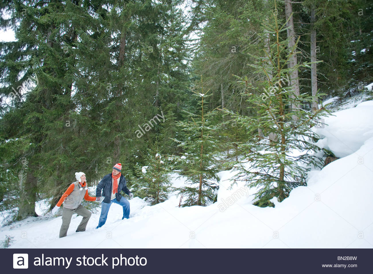 Couple holding hands and climbing slope in snowy woods - Stock Image