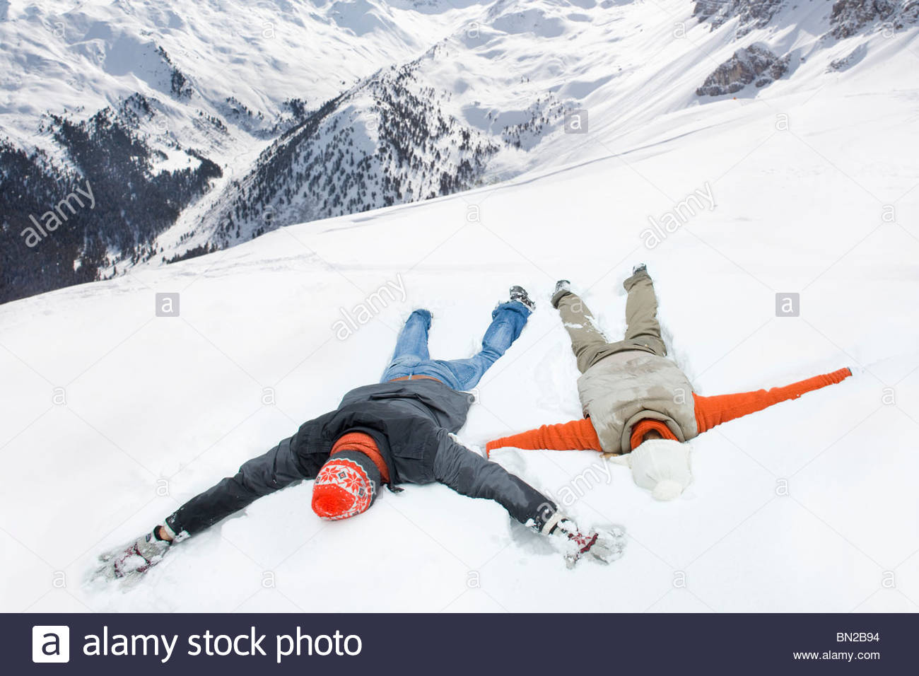 Couple making snow angels on mountain - Stock Image