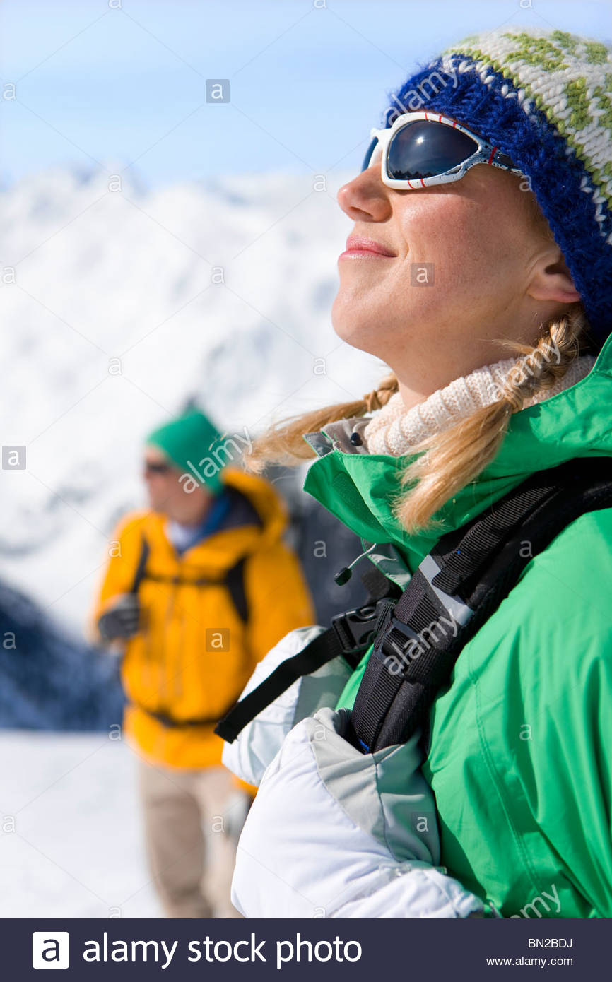 Happy woman with backpack enjoying sunshine on snowy mountain - Stock Image